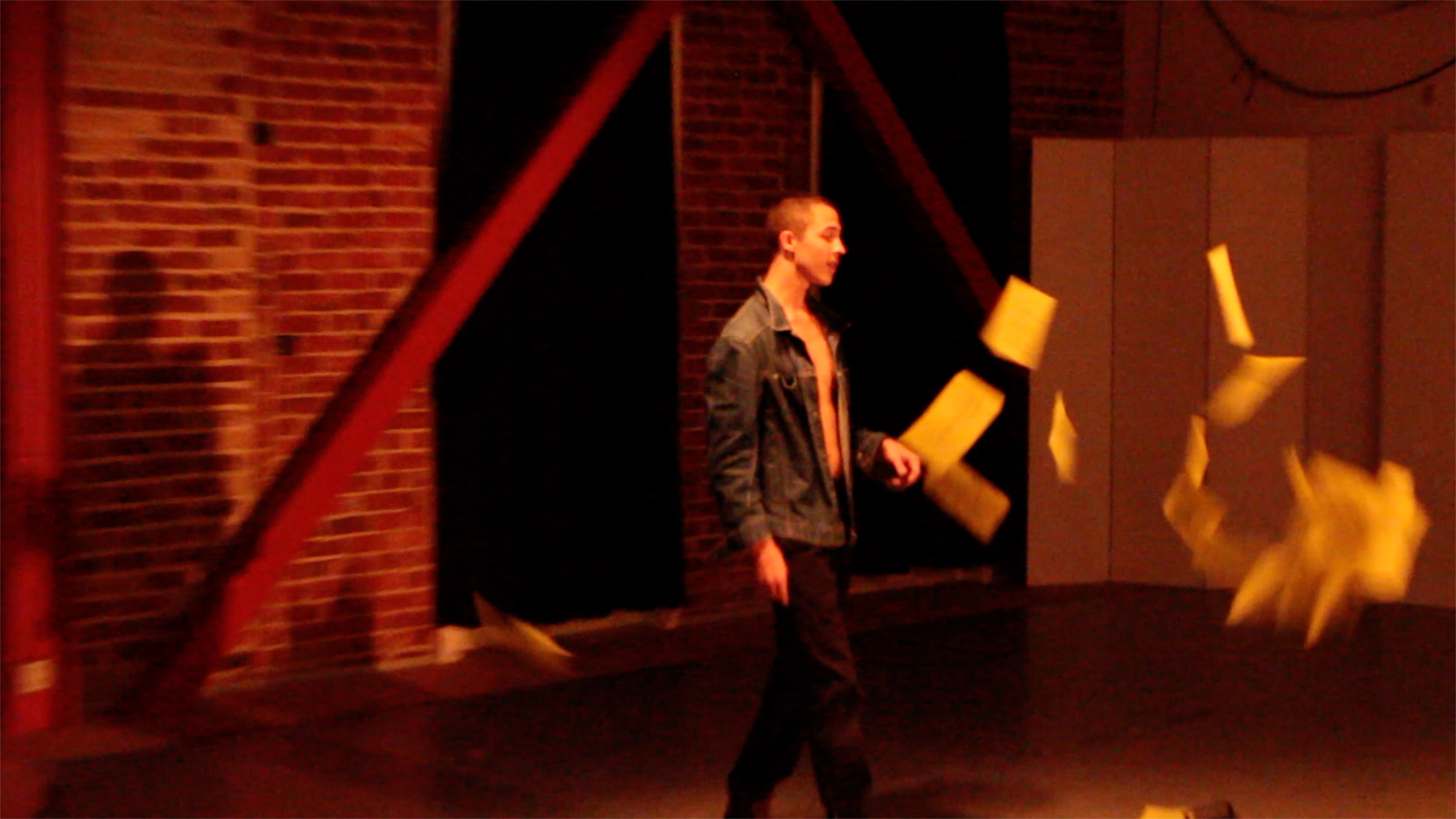 Dalton Alexander stands in a jean jacket, black dickie pants, and boots as yellow papers fly in front of him on their way to the ground.
